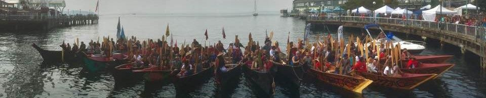 photo of people in Native American canoes in Elliott Bay