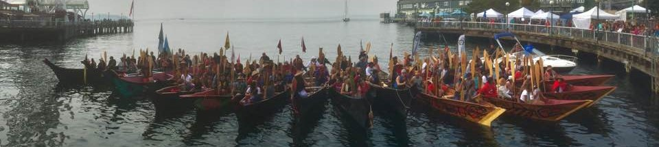 photo of people in Native American canoes in Elliott Bay