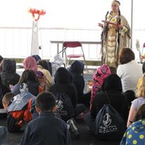 photo of children sitting and watching Native American performer