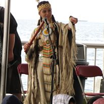 photo of Native American woman holding a small instrument
